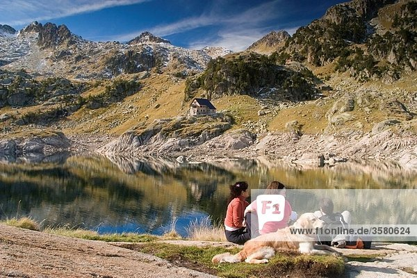 people near the Bigger Lake of Colomer and Colomer I mountain hut Colomers glaciar cirque Aran Valley Pyrenees mountain range Lerida province Catalonia  Spain  Europe