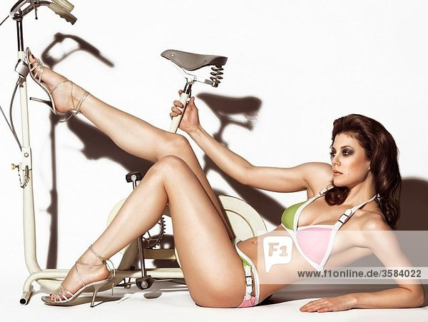 Young woman in a trendy swimsuit posing with a retro exercise bike Edgy high fashion photo