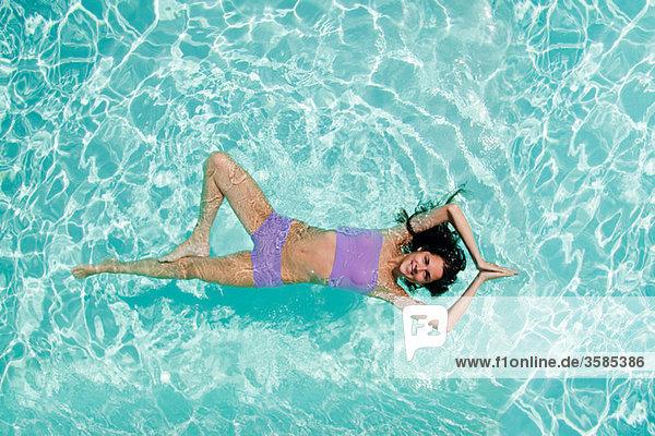 Frau praktiziert Yoga im Schwimmbad