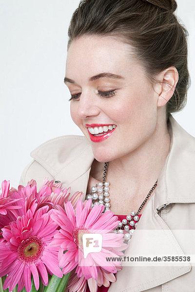 Junge Frau mit Gerbera-Blüten
