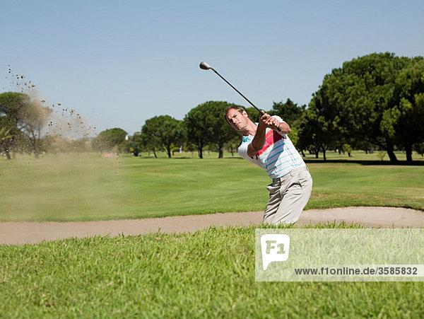 Mann spielt Golf  steckt im Bunker.