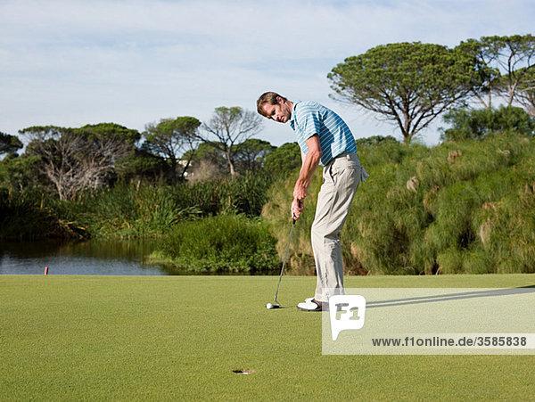 Man spielen Golf  auf Putting green