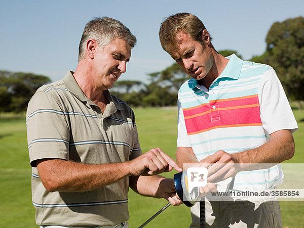 Zwei reife Männer spielen zusammen Golf.