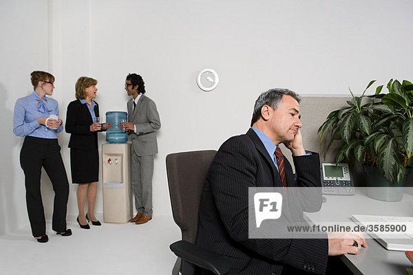 Geschäftsmann am Schreibtisch mit anderen tratschend mit Wasserkühler