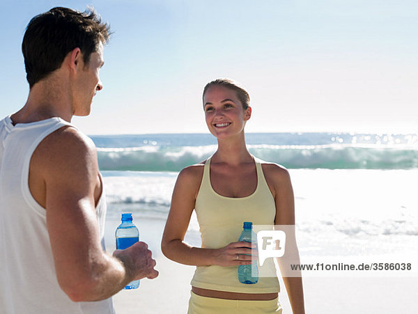 Junges Paar mit Wasserflaschen am Strand