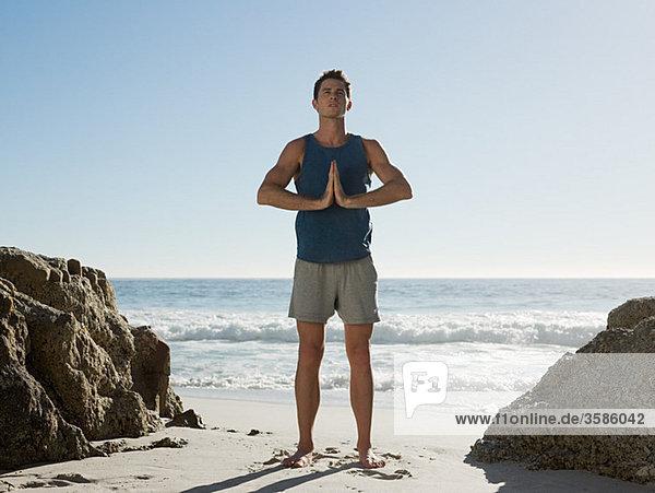 Junger Mann tun Yoga am Strand