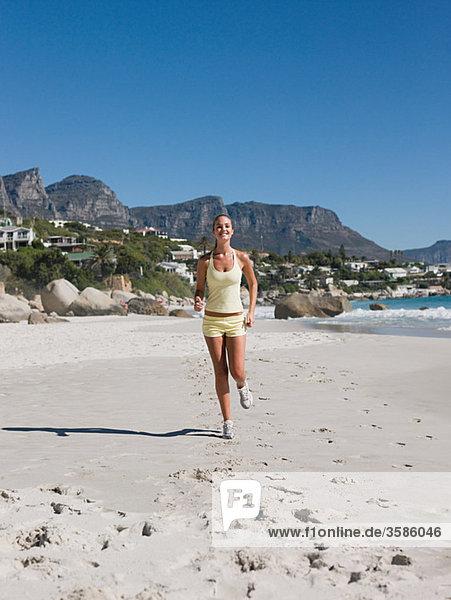 Junge Frau joggen am Strand