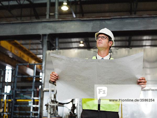 Reifer Mann mit Bauplan in der Fabrik