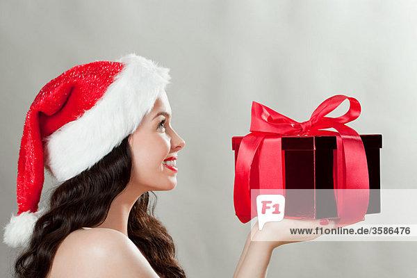Junge brünette Frau mit Weihnachtsmütze und Weihnachtsgeschenk