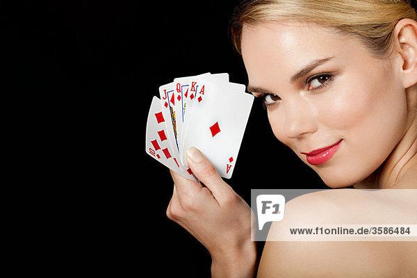 Junge blonde Frau beim Kartenspielen