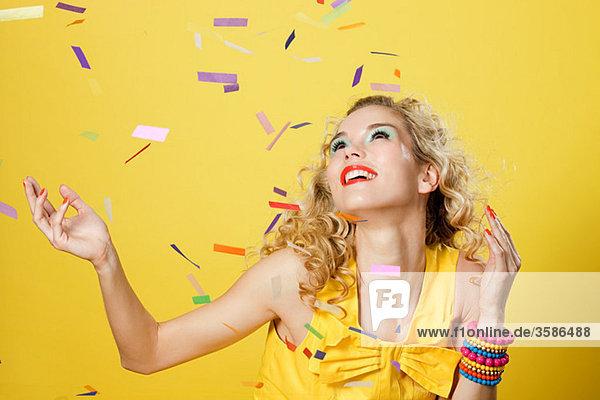 Junge blonde Frau mit buntem Konfetti
