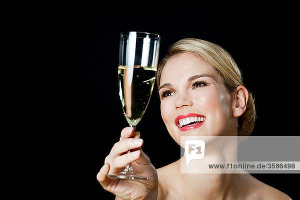 Junge blonde Frau mit Champagnerglas