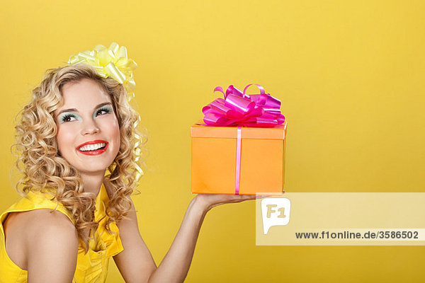 Junge blonde Frau mit Geburtstagsgeschenk vor gelbem Hintergrund