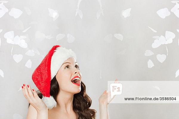 Junge brünette Frau mit Weihnachtsmütze und Konfetti