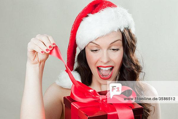 Junge brünette Frau mit Weihnachtsmütze Eröffnung Weihnachtsgeschenk