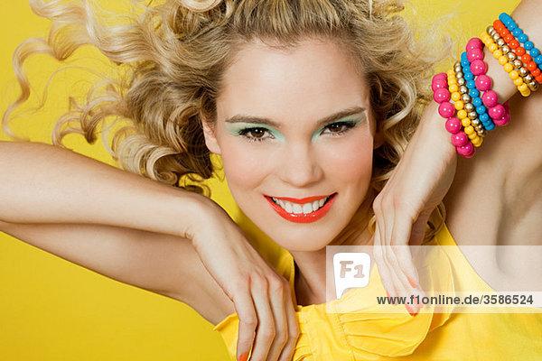 Junge blonde Frau vor gelbem Hintergrund