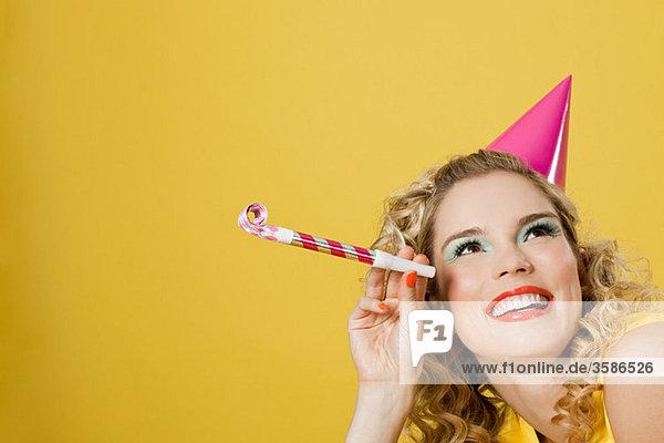 Junge Frau mit Partyhut und Partygebläse