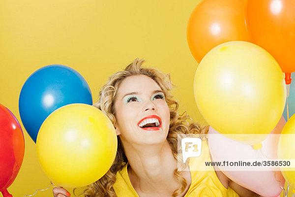 Junge blonde Frau mit Luftballons vor gelbem Hintergrund