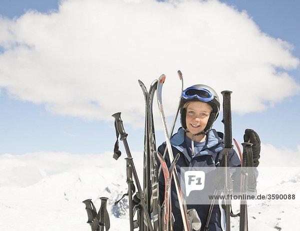 Junge mit Skiern in der Bergwelt