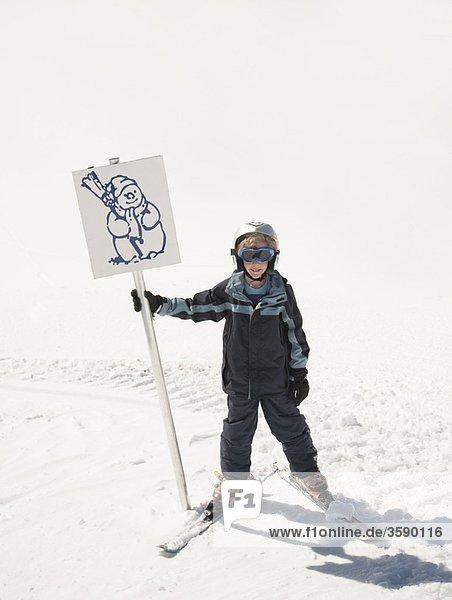 Boy skier holding snowman sign