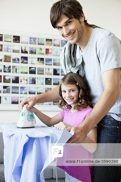 Father and daughter ironing