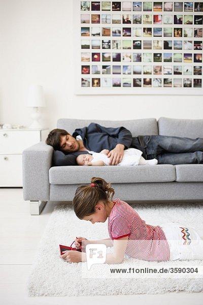 Mädchen spielt  während Vater sich ausruht