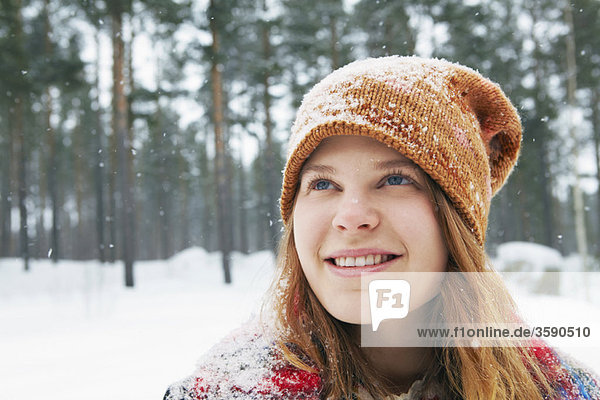 Smiling young woman watching snow fall