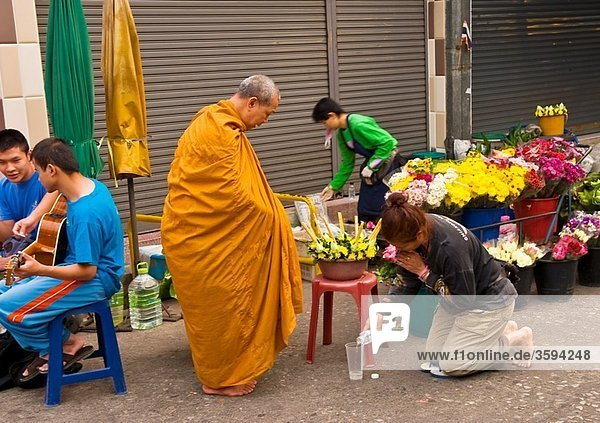 Buddhist monk giving blessings after receiving alms  Ton Payom Market  Chiang Mai  Northern Thailand