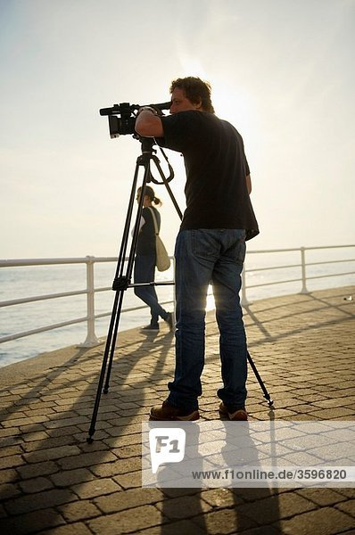 A man making a video recording with his camera on a tripod  Aberystwyth Wales UK