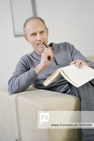 Porträt eines Mannes  der ein Buch hält und lächelt
