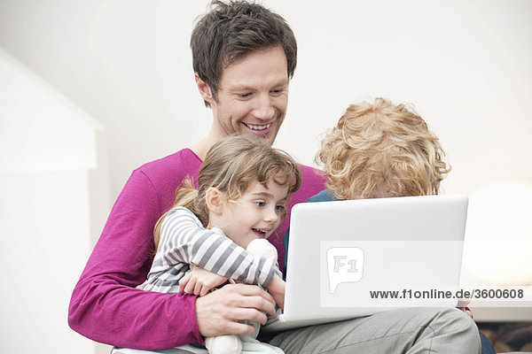 Close-up of a man assisting his son and daughter in using a laptop