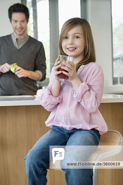 Girl drinking juice with her father standing behind her