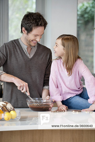 Man stirring a mixture in a bowl with his daughter