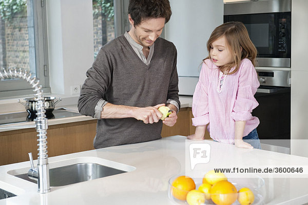 Man preparing breakfast with his daughter standing with him