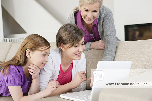Zwei Mädchen  die einen Laptop auf einer Couch benutzen  während ihre Großmutter neben ihnen steht.