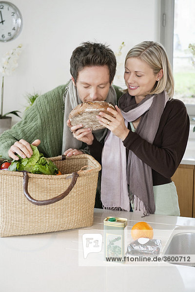 Man smelling a loaf of bread with his wife standing beside him