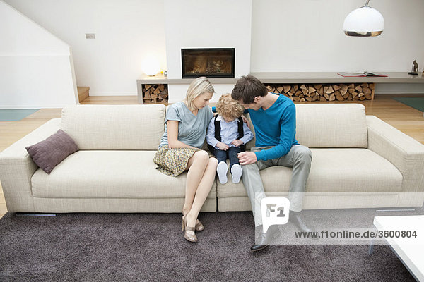 Parents sitting on a couch with their son