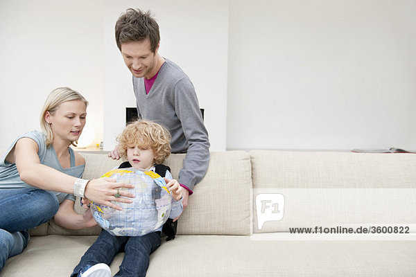 Parents in a living room with their son holding a globe