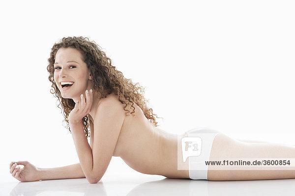 Porträt einer Frau  die sich auf Ellenbogen lehnt und lacht