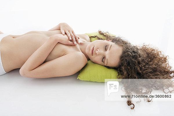 Frau  die ihre Brüste bedeckt und schläft.
