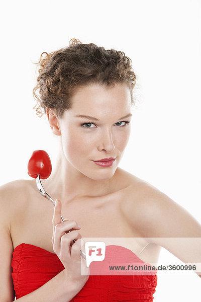 Porträt einer Frau mit einer Tomate auf einer Gabel