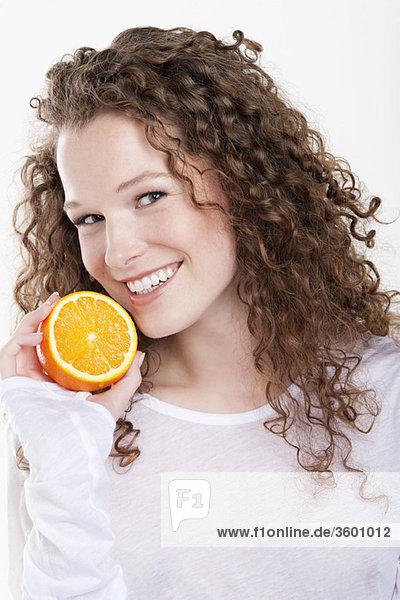 Porträt einer Frau mit einer halben Orange