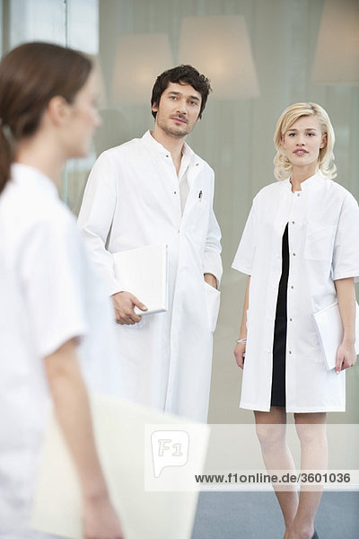 Male doctor standing with two female doctors
