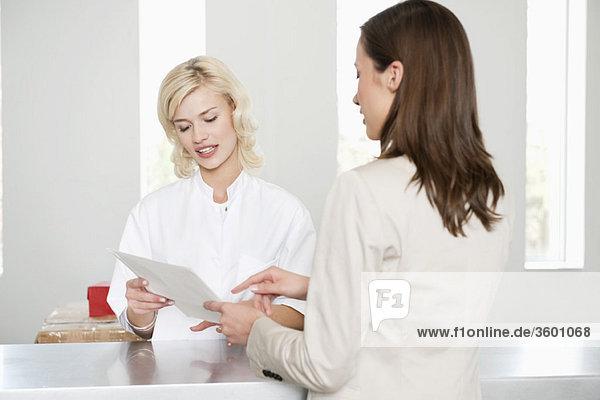Frau mit einer Krankenschwester  die einen medizinischen Bericht untersucht.