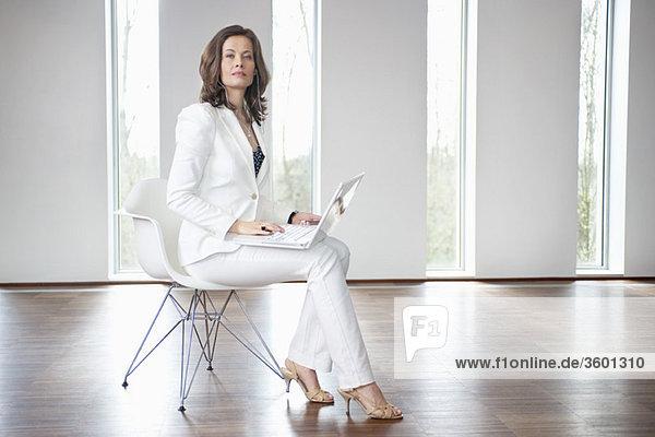 Geschäftsfrau sitzt auf einem Stuhl und benutzt einen Laptop
