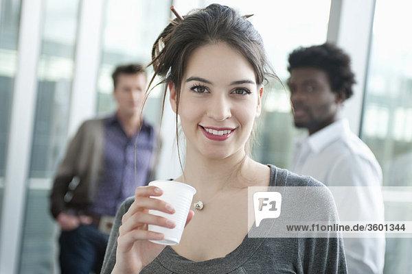 Geschäftsfrau mit Einwegbecher und Kollegen im Hintergrund