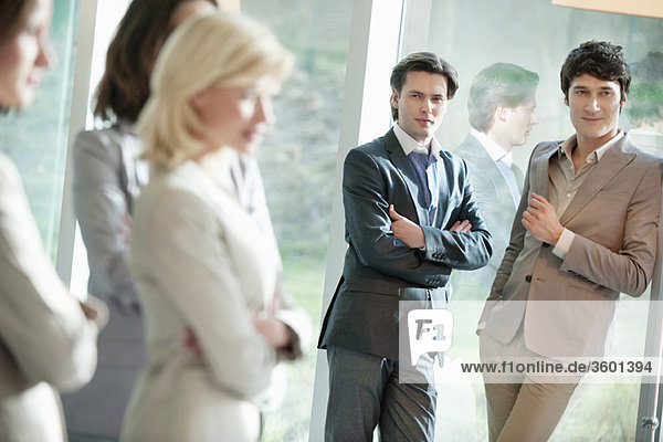 Two businessmen looking at their female colleagues