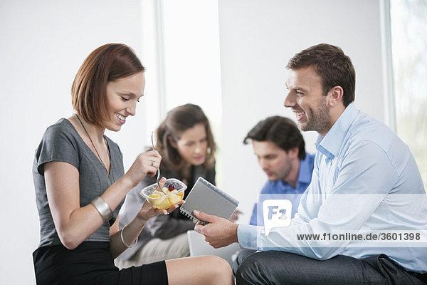 Frau isst Essen mit ihren Kollegen  die mit ihr sitzen