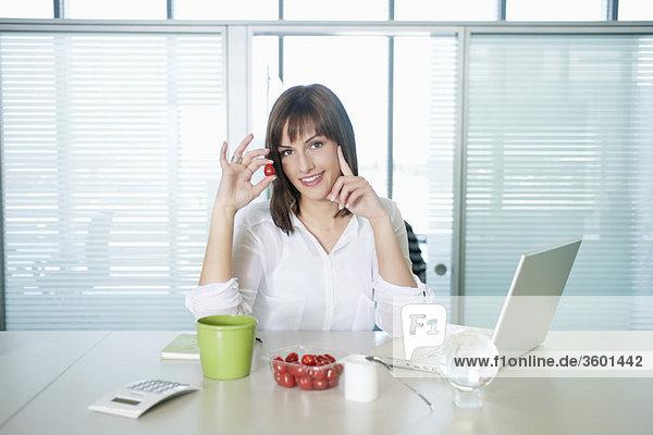 Geschäftsfrau hält eine Kirschtomate und lächelt