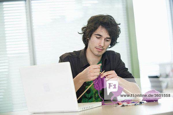Geschäftsmann beim Stricken vor dem Laptop